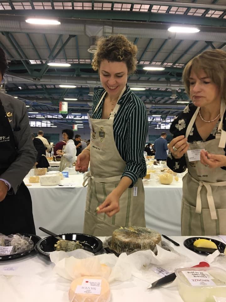Synne står foran et ostebord i en konkurranse for kåring av verdens beste ost